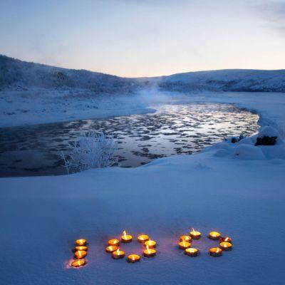 Kynttilöitä talvimaisemassa.