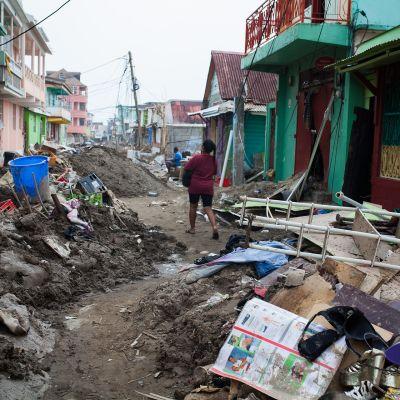 Tuhoja Dominican pääkaupungin kaduilla. Kadulla on hirmumyrskyn ympäriinsä heittelemää romua. Nainen kävelee kadulla kantaen jotain.