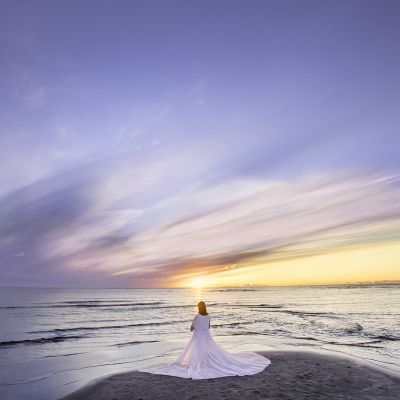 Valkoisiin pukeutunut nainen seisoo meren rannalla auringonlaskiessa