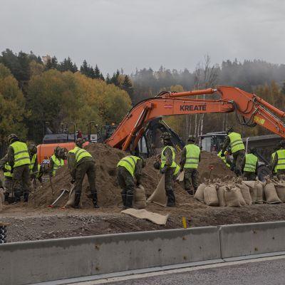 Puolustusvoimat täyttämässä hiekkasäkkejä Turunväylän tulva-alueella.