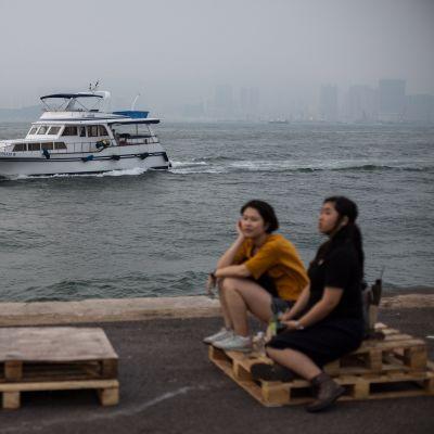 Naisia istuu merenrannalla. Ilmansaaste on peittänyt vastarannan näkyvist.