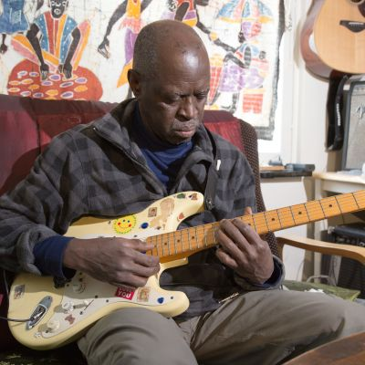 Senegalilainen muusikko Badu Ndjai soittaa nojatuolissa kitaraa.