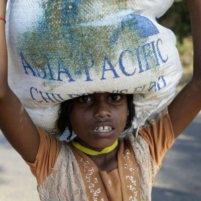 Rohingya-tyttö kantaa säkkiä.