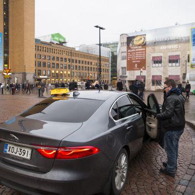 Taksi ja ihmisiä Rautatientorin taksitolpalla.