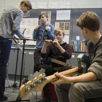 Pojat soittavat bassoa ja virittelevät mikrofoneja.