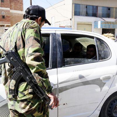 Mies rynnäkkökiväärin kanssa tarkastaa valkoista autoa.