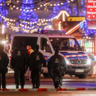 Poliisit kävelevät, taustalla poliisiauto ja joulukoristeita.
