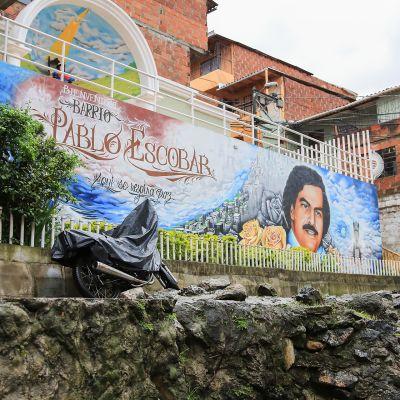 """""""Täällä hengitetään rauhaa"""" lukee seinämaalauksessa Pablo Escobarin nimeä kantavassa lähiössä. Muraalin yläpuolella on Escobarin äidin Meksikosta tuoma Kristus-lapsipyhimys."""