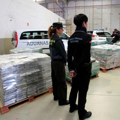 Poliisivirkailijat vartioivat takavarikoituja huumepakkauksia.