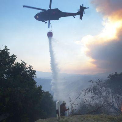 Palomies katsoo, kun helikopterista pudotetaan vettä palavaan maastoon.