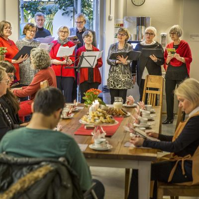 kuoro laulaa kahvipöydässä istujille