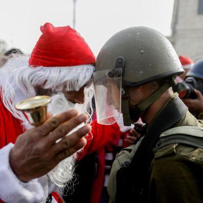 Israelilainen sotilas ja joulupukiksi pukeutunut palestiinalainen mielenosoittaja ottavat mittaa toisistaan otsa otsaa vasten.