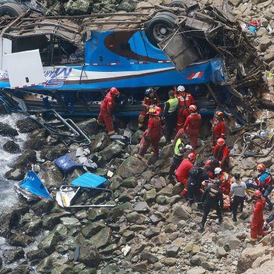 Ruhjoutunut bussi kivikossa, pelastustyöntekijöitä