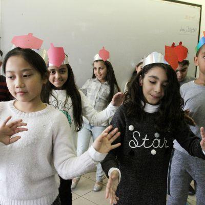 Lapset tanssivat luokkahuoneessa.