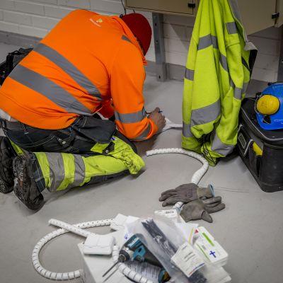 Sähköasentaja tutkii piirustuksia lattialla polvillaan.