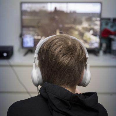 poika pelaa tietokonepeliä kuulokkeet päässä