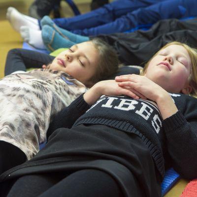 Lapset nukkuu koulun lattialla.