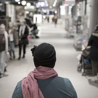 Nainen selin kauppakäytävällä.
