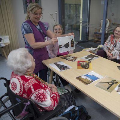 Askartelunohjaaja Marja Hietanen näyttää vanhaa valokuvaa pöydän ääressä istuville vanhuksille.