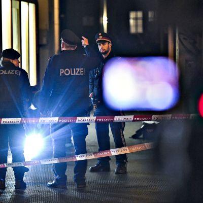 Poliiseja ja pelastushenkilöstöä pimeässä illassa Wienissä.