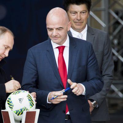 Vladimir Putin kirjoittaa nimikirjoitusta jalkapalloon.