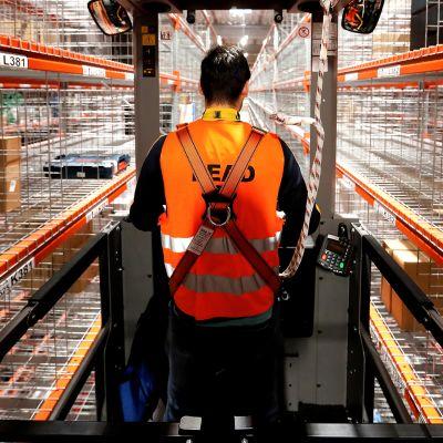 Työntekijä hyllyjen välissä Amazonin uudessa jakelukeskuksessa Wernessä, Saksassa.