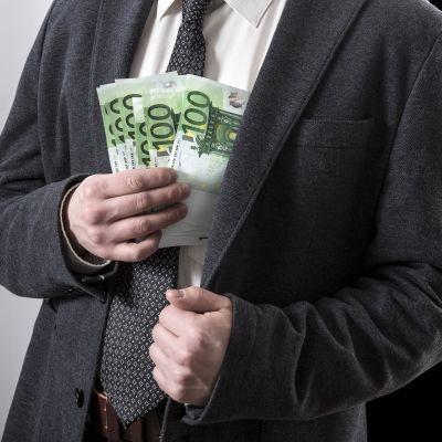 Mies laittaa setelinippua povitaskuun.