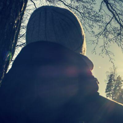 Nainen nojaa puuhun ja katselee kohti aurinkoa.