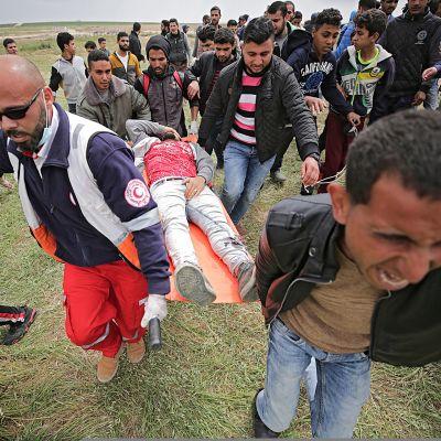 Palestiinalaiset kantavat haavoittunutta.