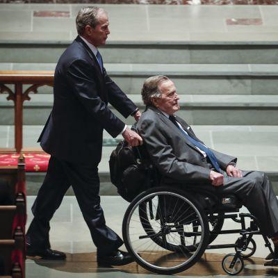 Yhdysvaltain entinen presidentti George W. Bush kuljettaa isäänsä myös entistä presidenttiä George Bushia pyörätuolissa äitinsä Barbara Bushin hautajaisissa.