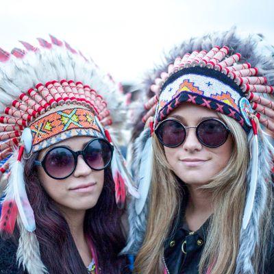 kaksi tyttöä intiaanipäähineissä