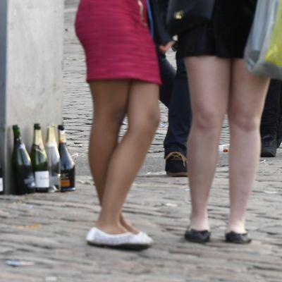 Unga kvinnor firar valborg. I bakgrunden tomma skumvinsflaskor.