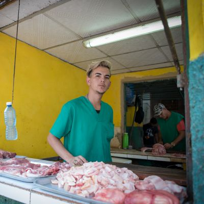 Nuori mies vihreässä t-paidassa katsoo kameraan. Edessä raakoja lihapaloja.