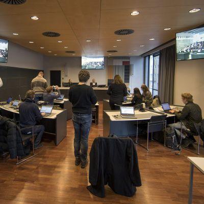 Toimittajat seuraavat Turun elokuisen puukkoiskun käsittelyä videonäytöiltä Turun oikeustalolla 17. huhtikuuta.