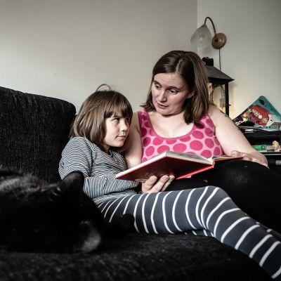 Ronja lukee sohvalla äidin kainalossa.