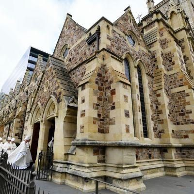 Katolinen kirkkorakennus Australiassa, kauempana kuvassa kävelee katolisisa pappeja.