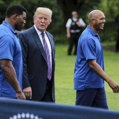 Presidentti Donald Trump seurassaan entinen amerikkalaisen jalkapallon tähti Herschel Walker ja entinen baseball-pelaaja Mariano Rivera Valkoisen talon järjestämässä kuntoilutapahtumassa.