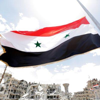 Syyrian lippu liehuu taisteluissa pahoin kärsineessä kaupunginosassa Damaskoksen eteläosassa.