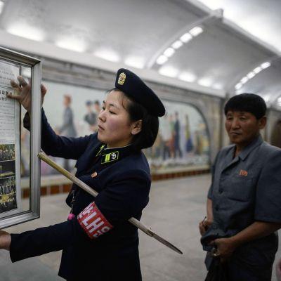 Pohjoiskorealainen virkailija vaihtaa uutissivua ilmoitustaululle metroasemalla Pyongyangissa.
