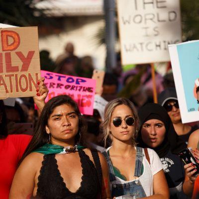 """Mielenosoittajat vastustavat Trumpin ajamaa """"nollatoleranssi""""-siirtolaispolitiikkaa."""
