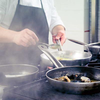 Ravintolan keittiössä paistetaan ruokaa hellan ääressä.