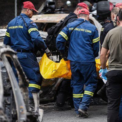 Kreikkalaiset pelastustyöntekijät kantavat ruumispussia Matin kaupungissa.