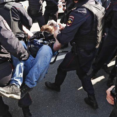 Venäläiset poliisit kantavat nuorta miestä poliisautoon.