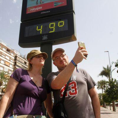 Turistit ottivat selfien lämpömittarin edessä Cordobassa, Espanjassa 1. elokuuta.