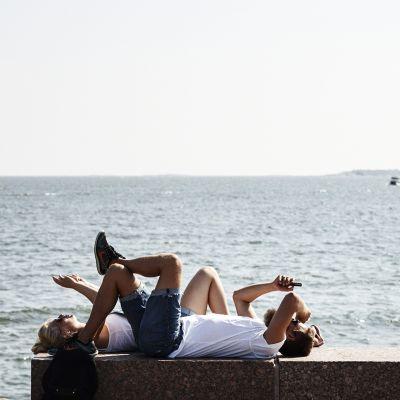 hmiset viettävät kuumaa kesäpäivää merenrannalla.