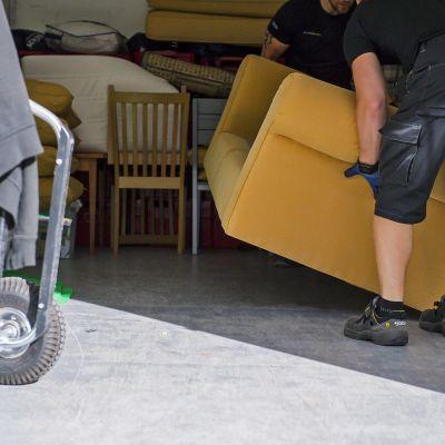 Muuttomiehet nostavat nojatuolia.