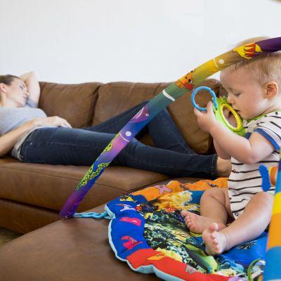 Pieni lapsi leikkii, väsynyt äiti nukahtanut sohvalle.