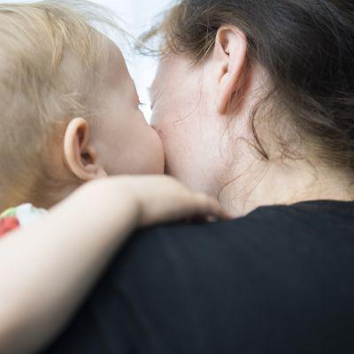 Lapsi antaa suukon äidille.