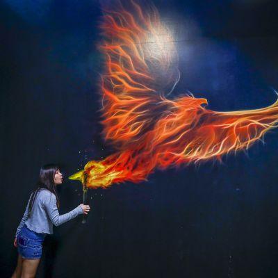 Nainen syöksee tulta taidenäyttelyssä