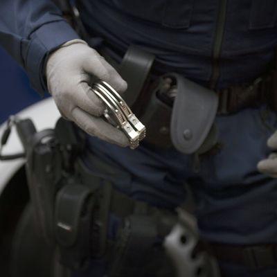 Käsiraudat poliisin kädessä.